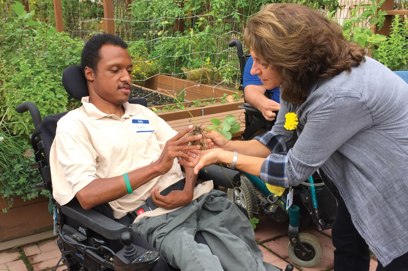 A community member participates in horticultural therapy with Anne Meore, Registered Horticultural Therapist.